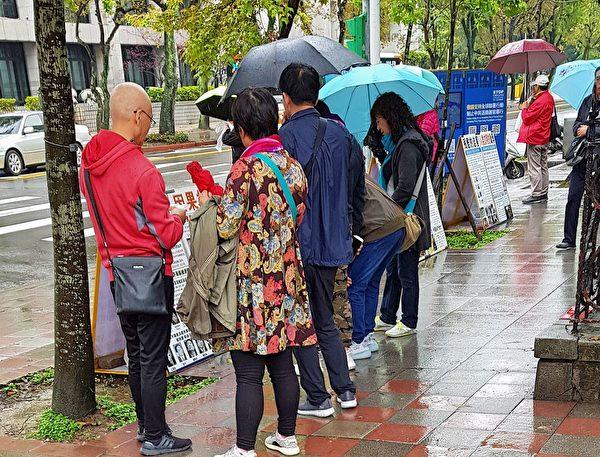 在雨中大陸遊客在閱讀真相展板。(明慧網)