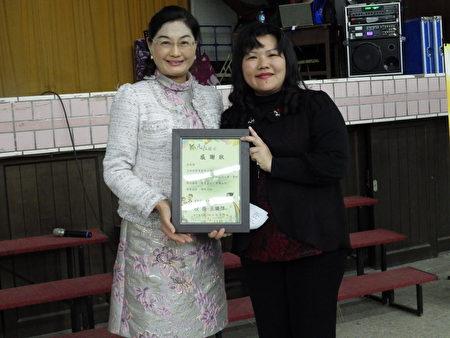 校长王晓萍(右)颁赠感谢状给艾琳诺实业有限公司董事长吴怡萱(左)。(廖素贞/大纪元)