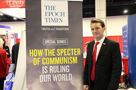 加州大學的威廉姆斯(Hayden Williams)喜愛大紀元特刊《魔鬼在統治著我們的世界》,主動到大紀元展位上要求合照。他在特朗普總統演講時被邀請上台講話。(林樂予/大紀元)