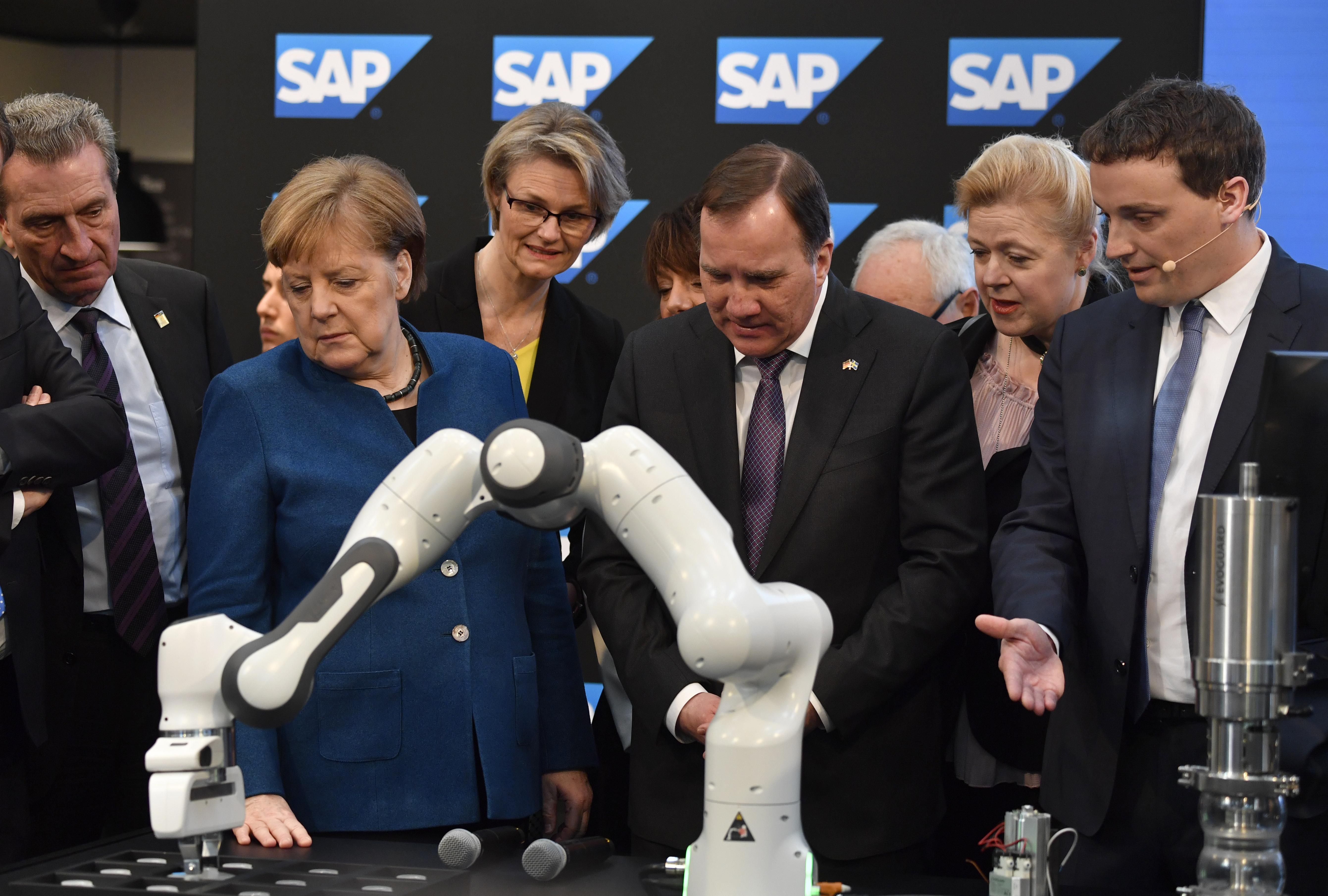 4月1日,默克爾在展會上參觀新科技產品。(John MACDOUGALL/AFP)