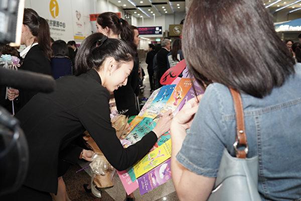 2019年4月1日晚上,神韻世界藝術團抵達台灣高雄小港國際機場,受到粉絲熱烈歡迎,圖為主要領舞演員杜增美幫粉絲簽名。(鄭順利/大紀元)