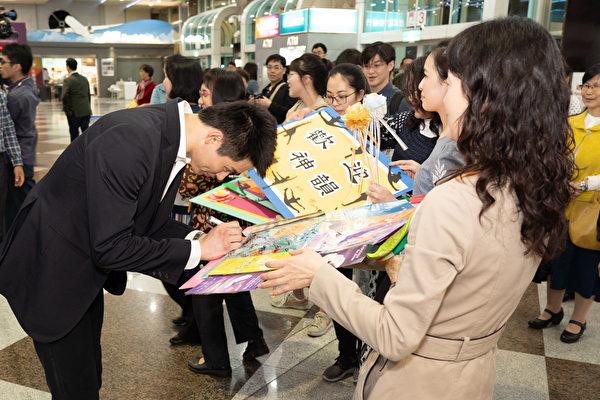 2019年4月1日晚上,神韻世界藝術團抵達台灣高雄小港國際機場,受到粉絲熱烈歡迎,圖為主要領舞演員陳厚任幫粉絲簽名。(鄭順利/大紀元)