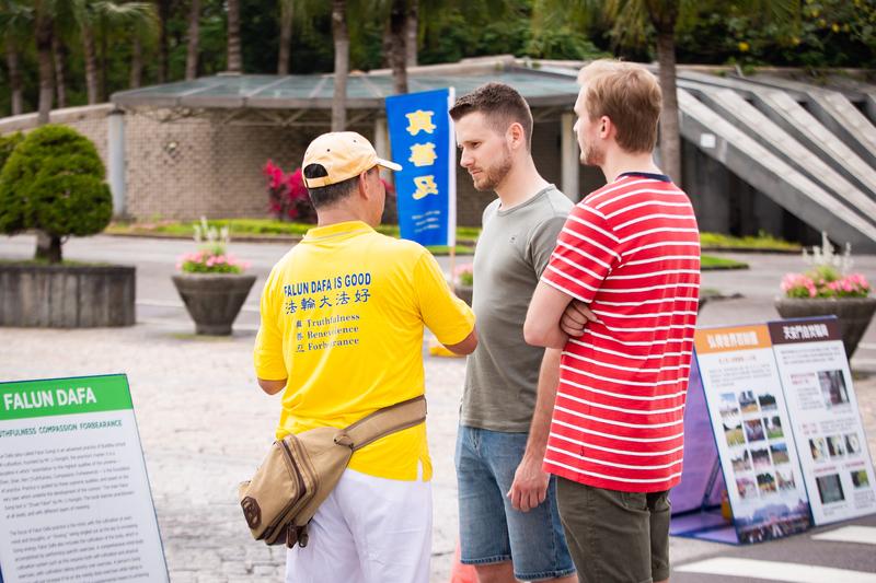 台灣部份法輪功學員4月21日在台北市民廣場舉辦「紀念中國大陸法輪功學員425和平上訪20周年」活動,圖為法輪功學員向外國遊客介紹法輪功。(陳柏州/大紀元)