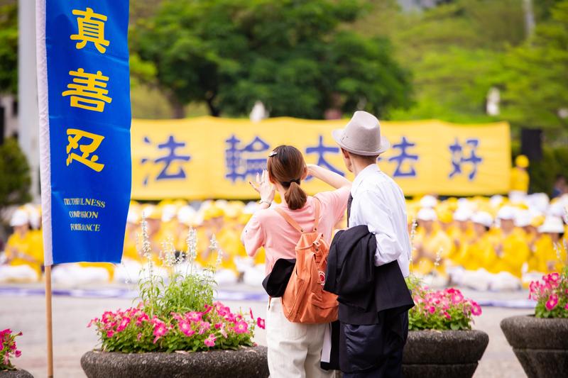 台灣部份法輪功學員4月21日在台北市民廣場舉辦「紀念中國大陸法輪功學員425和平上訪20周年」活動,圖為遊客駐足拍攝法輪功學員演煉五套功法。(陳柏州/大紀元)
