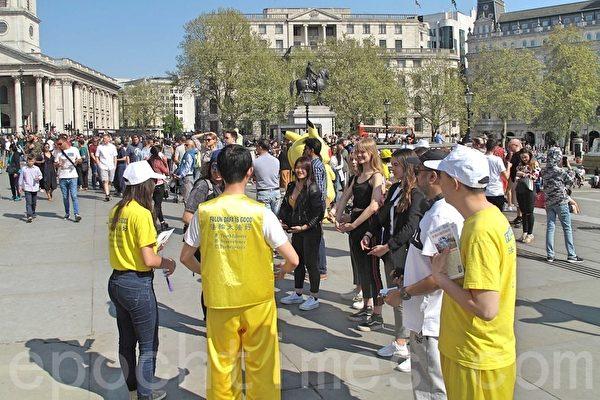 一群來倫敦旅遊的法國年輕人在現場嘗試學煉法輪功第二套功法動作。學員問他們第一次嘗試煉功的感受時,她們回答:感到「美好」、「平和」、「愉悅」。(方元/大紀元)