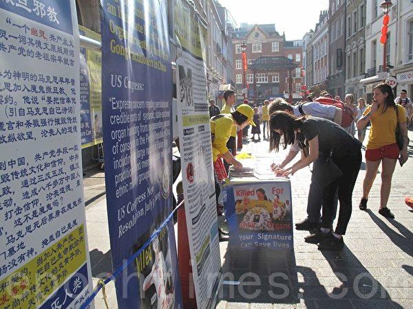 2019年4月21日,英國法輪功學員在倫敦唐人街煉功、發傳單講真相,明白真相的民眾簽名支持法輪功學員反迫害。(方元/大紀元)