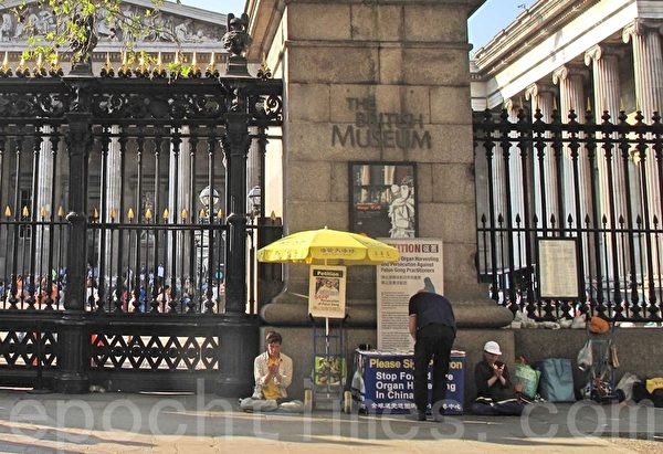 2019年4月21日,大英博物館門前,兩位法輪功學員在打坐,一位西人默默走過來簽名。(方元/大紀元)