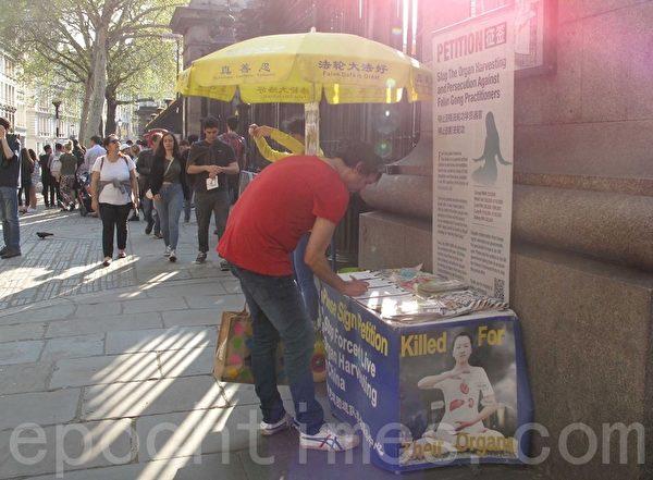 希臘人安東尼(Anthony)在大英博物館門前簽名支持法輪功學員反迫害。(方元/大紀元)