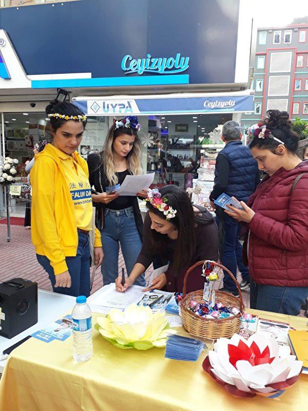 三位女子杜納、艾茲格和納林在請願書上簽名。(明慧網)