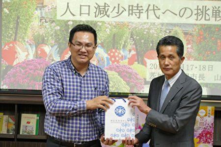 暨大校方代表(左)致赠笠间市市长山口伸树(右)纪念品。