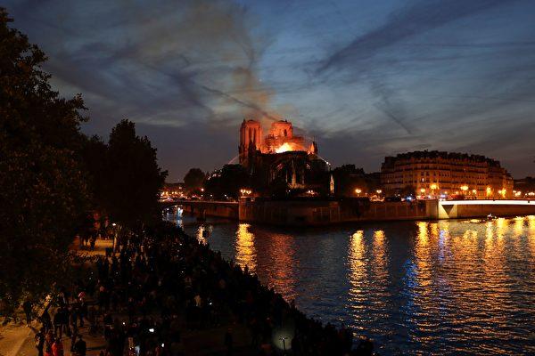 夜幕低垂,火焰照亮天際,同時倒映在塞納河平靜的水面上。(Thomas SAMSON/AFP)