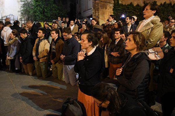 周一晚上,在巴黎的人們為聖母院祈禱。(ERIC FEFERBERG/AFP/Getty Images)