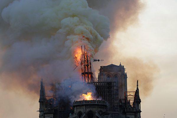 在這張聖母院火災照片中,網友說在塔尖的左方似乎出現一個人臉。(GEOFFROY VAN DER HASSELT/AFP/Getty Images)