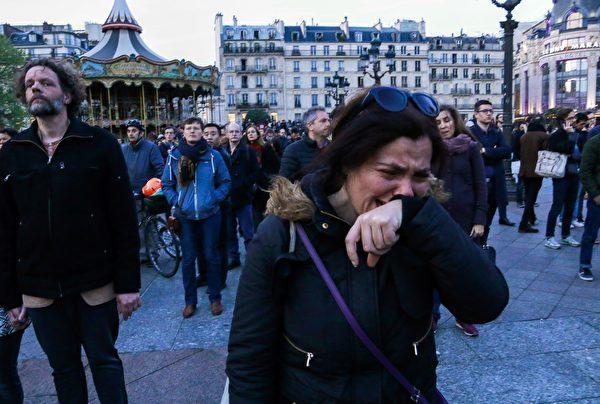 看到聖母院塔尖崩塌,法國民眾哭泣。 (GEOFFROY VAN DER HASSELT/AFP/Getty Images)