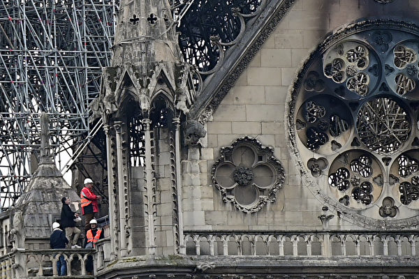 Inspectors are seen on the roof of the landmark Notre-Dame Cathedral in central Paris on April 16, 2019, the day after a fire ripped through its main roof. - A major fire broke out at the landmark Notre-Dame Cathedral in central Paris sending flames and huge clouds of grey smoke billowing into the sky, the fire service said. The flames and smoke plumed from the spire and roof of the gothic cathedral, visited by millions of people a year, where renovations are currently underway. (Photo by Lionel BONAVENTURE / AFP) (Photo credit should read LIONEL BONAVENTURE/AFP/Getty Images)