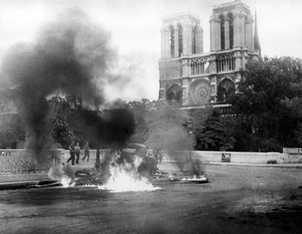 """A photo taken between 22 and 24 August 1944 in Paris during World War II shows a flaming vehicule close to the Pont Saint-Michel and the cathedral Notre-Dame part of the """"Battle of Paris"""" opposing the FFI (French Forces of the Interior) and remaining Nazi forces, a few days before the Liberation of the French capital city on August 25, 1944. Colonel Rol Tanguy, commander of the group the French Forces of the Interior in the Île-de-France, had posters put up on August 21 and 22 calling for barricades to be thrown up all over the city. AFP PHOTO (Photo by - / AFP) (Photo credit should read -/AFP/Getty Images)"""