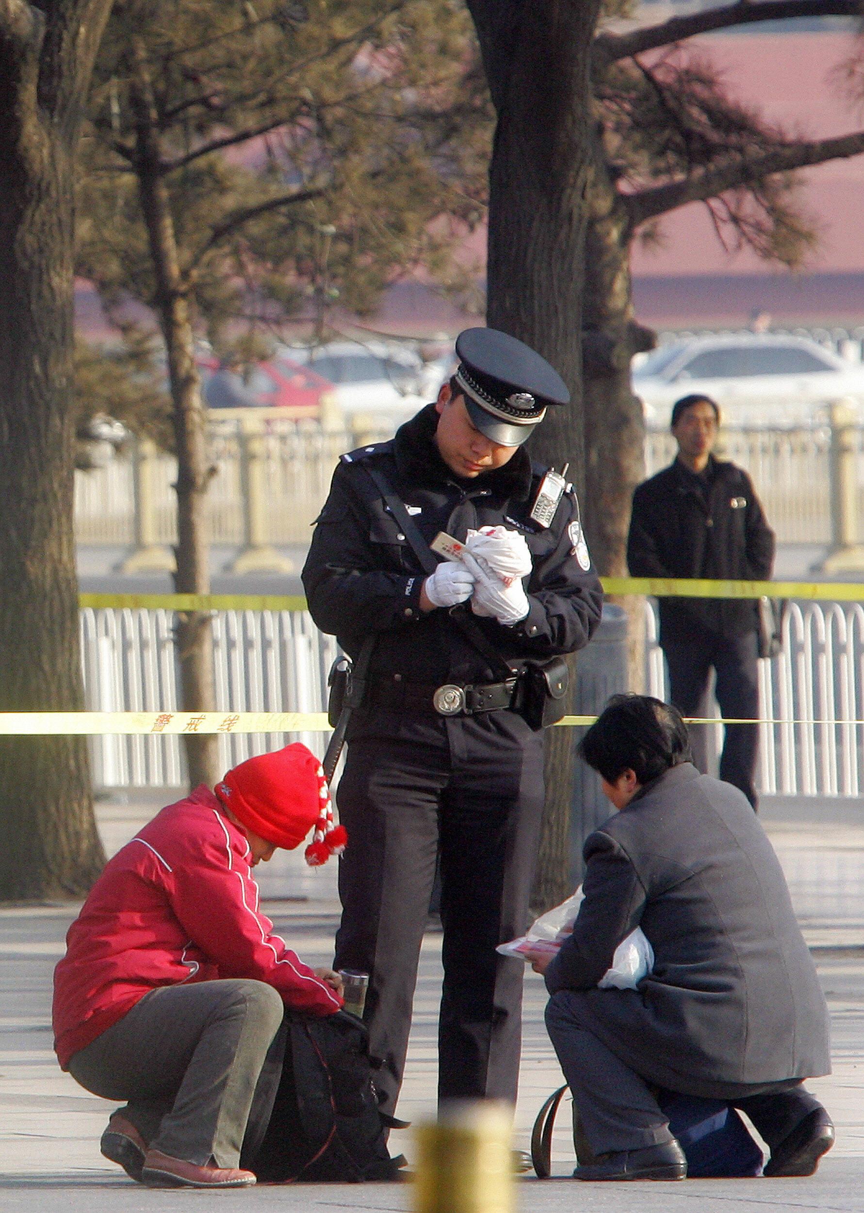 中共警察在北京人民大會堂附近檢查路人的身份證和隨身物品。(AFP/Getty Images)