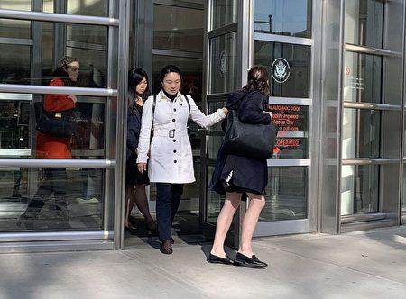林英(白外套)和律师(红外套)走出法庭。