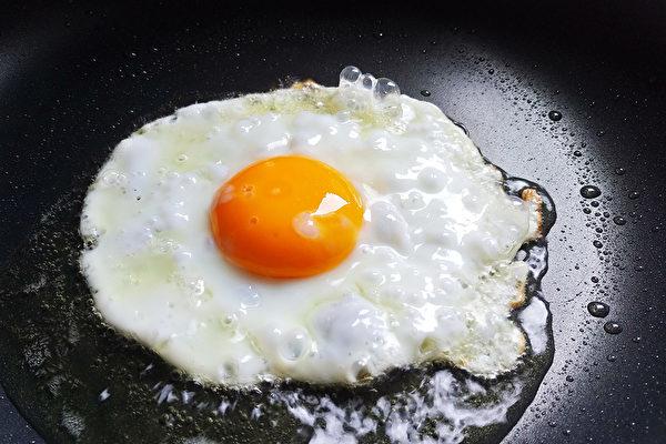 看到蛋白开始凝固时,可在鸡蛋上洒2小勺热水,马上盖上锅盖。(Shutterstock)