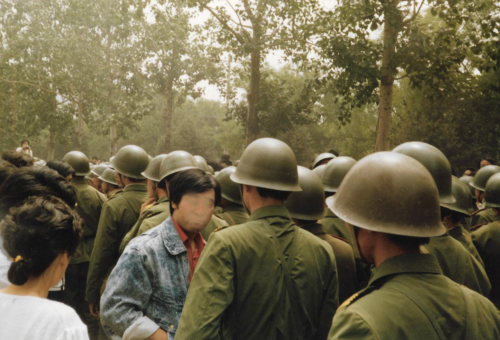 1989年6月3日上午,這些軍人打算拖回出事的軍車,被人們擋住。(王珍提供)