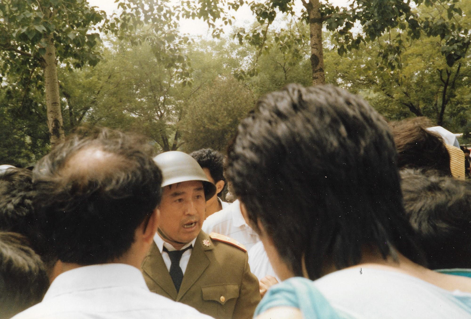 1989年6月3日上午,一路軍人在北京長安街木樨地受阻。他們要拖回壓死人的警車,被民眾阻攔。(王珍提供)