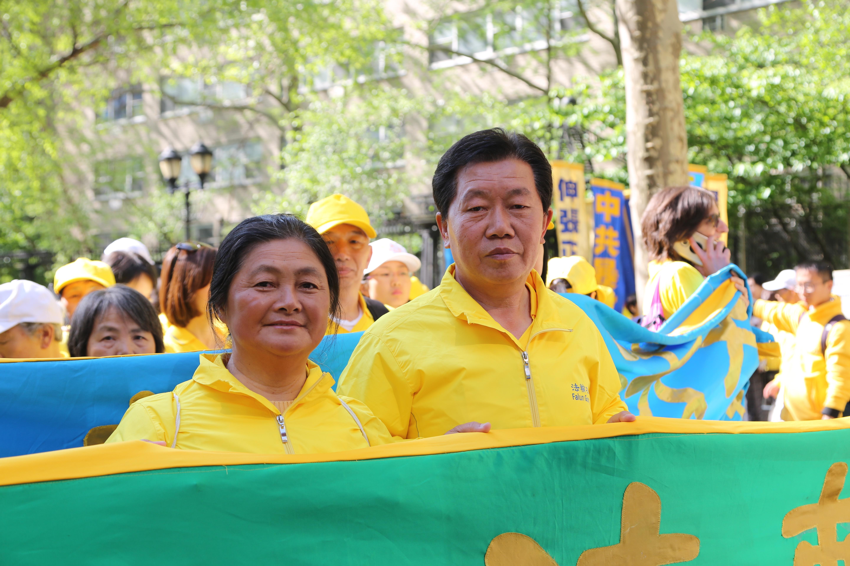 5月16日在遊行隊伍中的三藩市景點退黨義工劉志、韓華(左)夫婦。(施萍/大紀元)