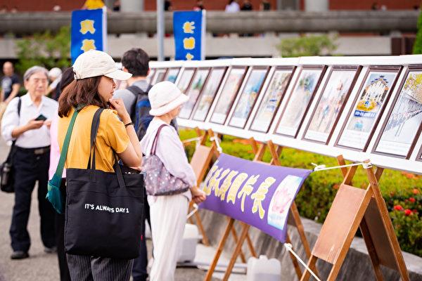 台北部份法輪功學員5月5日在國父紀念館前舉辦活動,歡欣慶祝法輪大法洪傳27周年。圖為民眾駐足觀賞法輪大法洪傳世界圖片展。(陳柏州/大紀元)