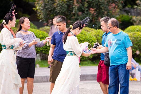 台北部份法輪功學員5月5日在國父紀念館前舉辦活動,歡欣慶祝法輪大法洪傳27周年。圖為仙女隊仙女向民眾傳遞大法的美好。(陳柏州/大紀元)