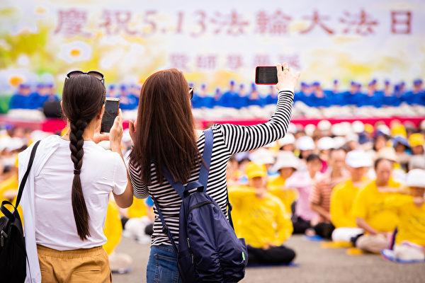台北部份法輪功學員5月5日在國父紀念館前舉辦活動,歡欣慶祝法輪大法洪傳27周年。圖為民眾駐足拍攝法輪功學員演煉功法。(陳柏州/大紀元)