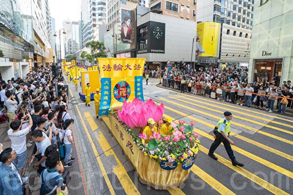 香港法輪功學員舉行集會遊行,慶祝世界法輪大法日。遊行隊伍途經尖沙咀廣東道,大批遊客和市民夾道觀看。(李逸/大紀元)