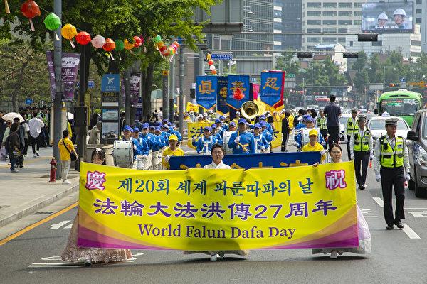 南韓部份法輪功學員首爾市中心舉行盛大遊行,慶祝世界法輪大法日。(全景林/大紀元)