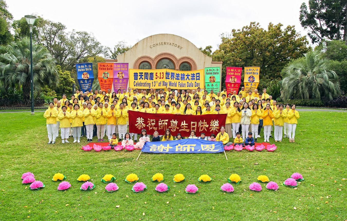法輪功學員在墨爾本市中心最著名的景點費茨羅伊公園合照,恭賀師父生日快樂,慶祝世界法輪大法日。(明慧網)