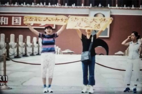 二零零一年,王易非(左二)和同修在天安門廣場舉著「法輪大法是正法」和「法輪大法好」的橫幅。(影片截圖)