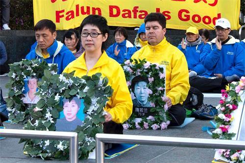 今年四月二十日,法輪功學員王易非手持被迫害致死的妹妹王可非的遺像。(大紀元)