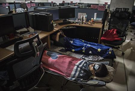 華為深圳總部員工桌子底下都有一個被褥,午飯後小睡,隨後他們要工作到晚上10點。(Kevin Frayer/Getty Images)