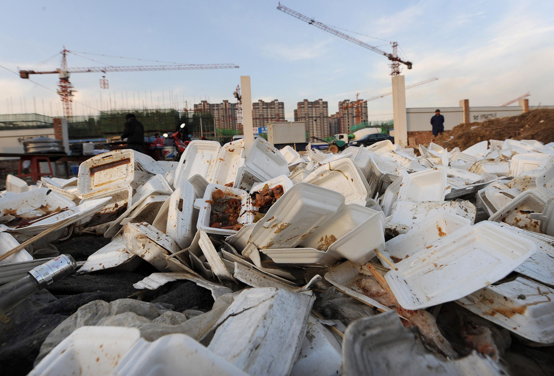 中國正在被餐盒、餐具和餐袋所淹沒。圖為2009年12月6日,安徽合肥一個建築工地附近的一堆廢舊白色塑料餐盒。(STR/AFP/Getty Images)