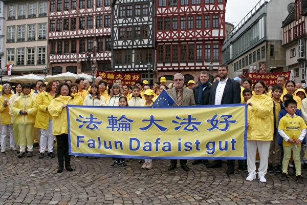 歐洲議會德國議員加勒(Michael Gahler)(前排持歐盟旗幟者)來到法蘭克福羅馬人廣場,和德國法輪功學員共同慶祝世界法輪大法日,支持法輪功反迫害。(曹工/大紀元)