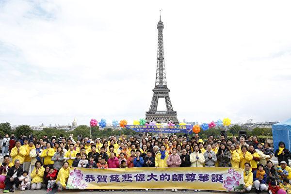 法國法輪功學員在巴黎鐵塔對面的人權廣場上合照,恭祝李洪志師父華誕。(章樂/大紀元)