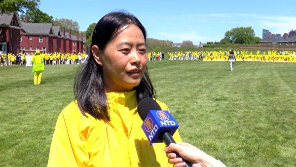2019年5月18日,1994年在廣州參加過李洪志先生傳功講法班的王婷婷在紐約總督島排字活動中受訪。(林丹/大紀元)
