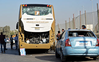 图为被炸弹袭击的旅游巴士和私家汽车。(Sayed Hasan/AFP/Getty Images)
