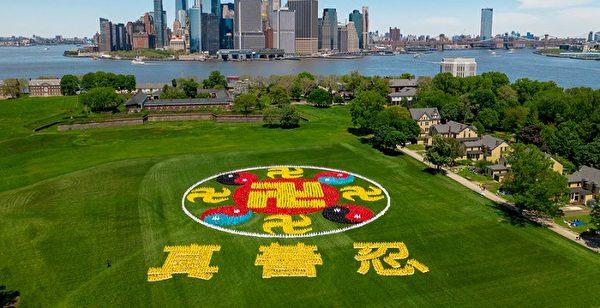 2019年5月18日,來自全球的部分法輪功學員會聚紐約,在紐約總督島排出「法輪圖形」和「真、善、忍」三字,慶祝世界法輪大法日。(新唐人電視台)