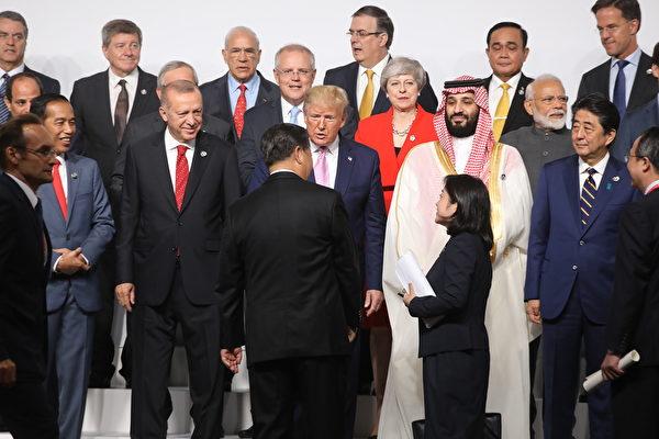 二十國集團(G20)峰會於周五(6月28日)在日本大阪揭幕,各國領袖齊聚一起拍攝大合照,其中中國國家主席習近平主動趨前與美國總統特朗普握手。(Ludovic MARIN/AFP)