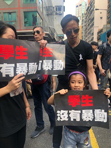 七歲小朋友不滿警方暴力,在家人陪同下首次上街。(梁珍/大紀元)