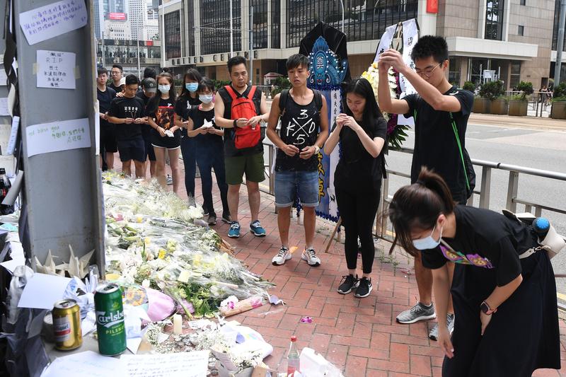 遊行會開始之前,市民到太古廣場悼念和獻花。(ANTHONY WALLACE/AFP/Getty Images)