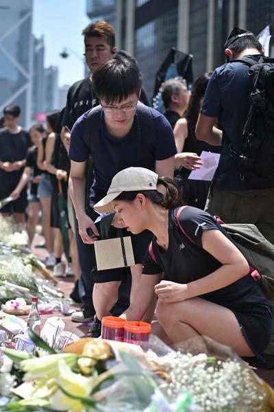 6月16日,香港新集會開始之前,市民在「反送中」不幸墮樓身亡死者地點附近悼念和獻花。(ANTHONY WALLACE/AFP/Getty Images)
