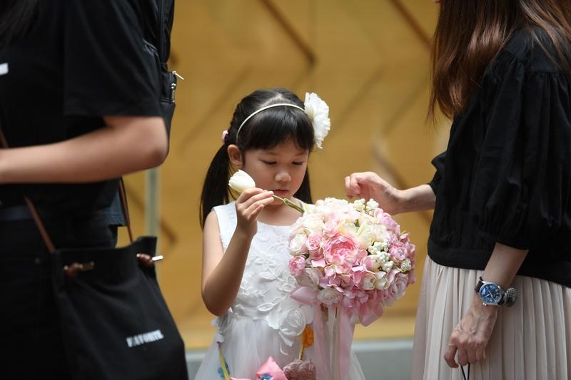 一名女孩準備將鮮花花束獻給死者。(ANTHONY WALLACE/AFP/Getty Images)