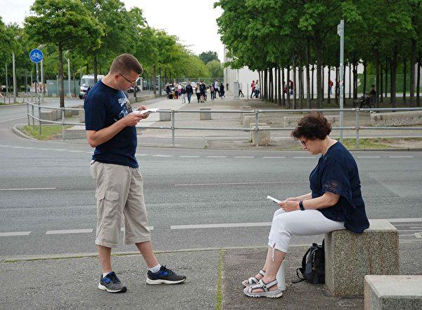 來自科布倫茨的兩位遊客在閱讀法輪功真相傳單。(明慧網)