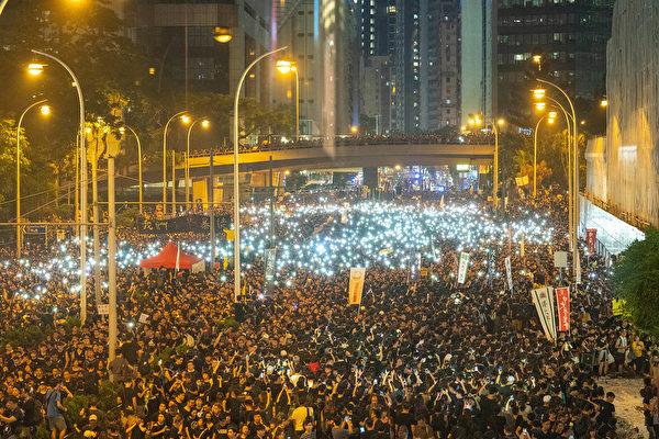 入夜後,市民以手機亮燈,猶如燃起點點燭光。(李逸/大紀元)