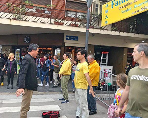 華人林先生(左)跟阿根廷學員學煉功法,臨走時表示煉法輪功的人都是好人,他認為共產黨盡做壞事、從不幹好事。(明慧網)