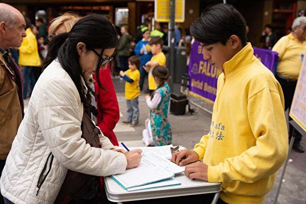 阿根廷民眾在請願信上簽字,要求停止在中國發生的對法輪功的迫害。(明慧網)